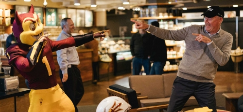 Sparky and Starbucks CEO Kevin Johnson point at each other at a fifth-anniversary celebration