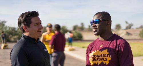 ASU students Leirbag Fajardo and Aki Olambiwonnu share a laugh while volunteering at the Borderlands Produce On Wheels With Out Waste event at the ASU Polytechnic campus