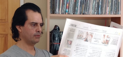 Image of Luis Benavides reading an upside down newspaper.