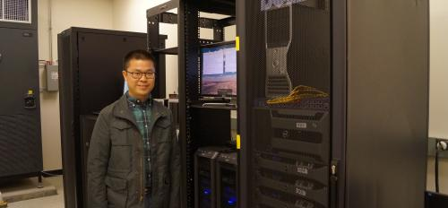 ASU graduate student Mingming Li standing in front of computer clusters