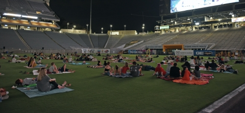 Frank Kush Field at night is scattered with families on blankets watching the video screen