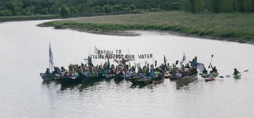 People gather in a river to protest in the movie Rise