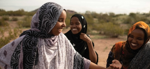 Three women in headscarves laugh together at Papago Park