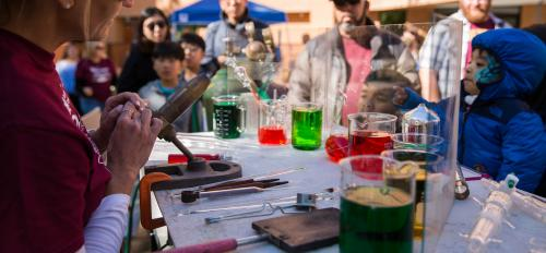 woman holding glass blowing tools with beakers of colored liquid on table while crowd watches