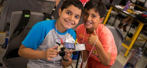 Two students hold up their creation from an engineering summer camp.