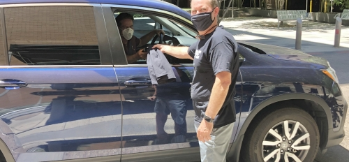 ASU Enterprise Partners CEO Dan Dillon wears shorts, a black t-shirt and black mask and passes out a black t-shirt to employee Peter Means through the passenger window of his blue vehicle. The employee wears a white face mask.