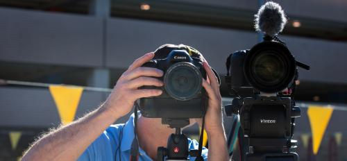 A man adjusts two video cameras