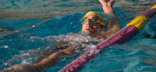 man swimming backstroke in a pool