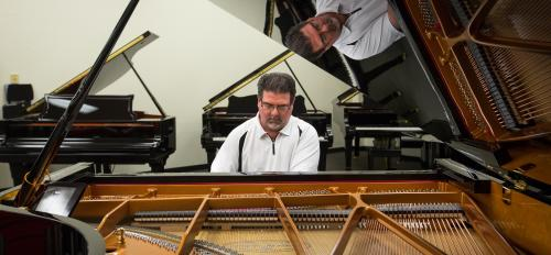 School of Music alum Jason Sipe plays a grand piano.