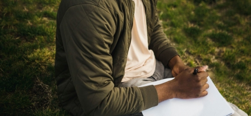Man sitting and writing on paper