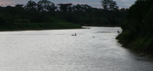 man crossing river in small boat