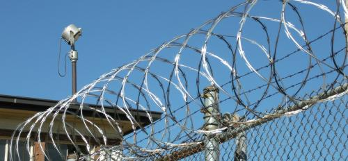 A prison fence with a security camera