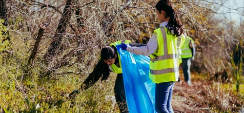 Two college age women wearing safety vests pick up trash on a riverbed and put it into a large trashbag
