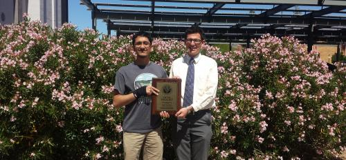 two students holding a plaque