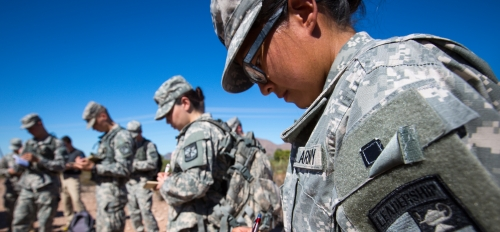 Army soldiers in fatigues take notes in a desert landscape