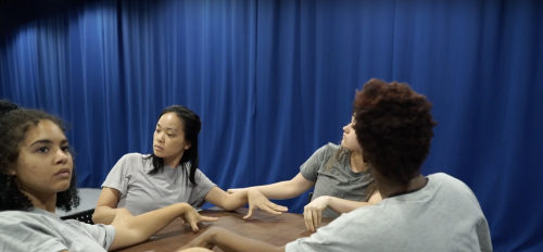 A screenshot from a video on the commons that shows four girls at a table