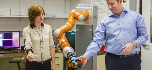 two people interacting with robotic arm