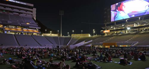 Family lie on blankets on the ASU football field to watch a Spider-Man movie