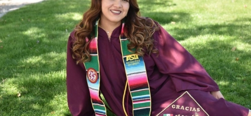 Picture of Maricela Diaz in cap and gown sitting on green grass in the shade