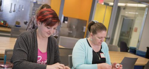 Two participants in the STEMteachersPHX Conference build prototype of a smartphone case