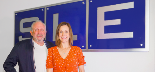 Steve LeVine and Jamie Morris LeVine in front of an SLE sign