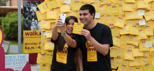 Students take a selfie in front of a board full of Sun Devil Giving Day notes.