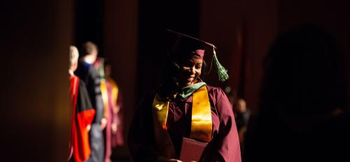 School of Sustainability graduate Farren Hinton walks at convocation