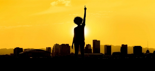 A woman holds her hands in the air with a sunset vista behind her