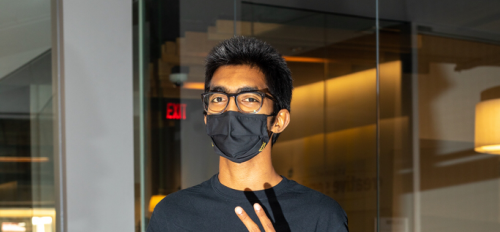 Venu Gopinath Nukavarapu in the MU with a mask, an ASU Student Life shirt and his camera giving a peace sign