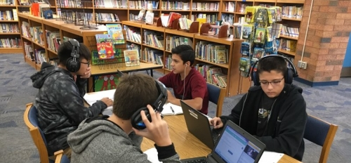 Four middle school students sit at a table in a school library logged in to a digital class, wearing headphones in front of laptops