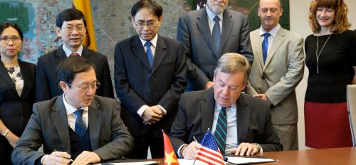 people signing papers at desk