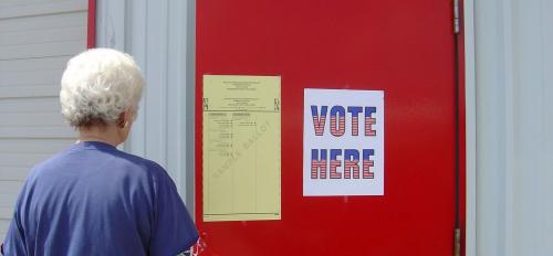 A woman opens a door to a voting location.