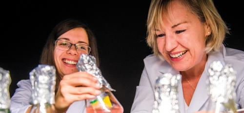 Two scientists examine beakers filled with different colored liquids