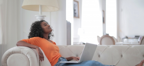 woman sitting on a couch with a laptop