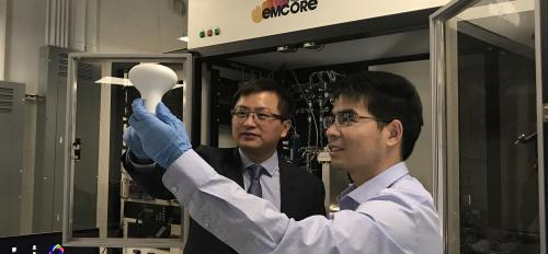 Yuji Zhao (left), an electrical engineering professor in Arizona State University's Ira A. Fulton Schools of Engineering, and Houqiang Fu (right), a doctoral student in Zhao's research group, hold an LED light bulb.