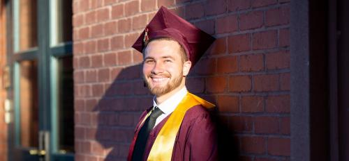 Yusef Sabri leans against the brick side of a building looking at the camera. He is wearing a maroon graduation gown and cap with a gold stole. He is smiling.