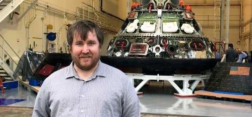 ASU alum Zachary Pirtle stands in front of an Orion spacecraft at NASA