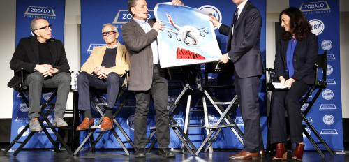 man being presented with movie poster on stage