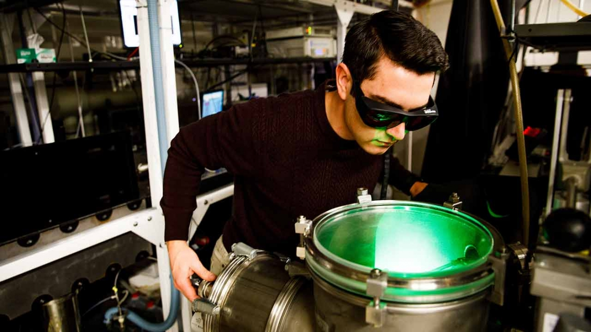 A student researcher in Scott Sayres' laboratory uses safety gear developed at ASU to conduct experimental research using ultrashort laser pulses.