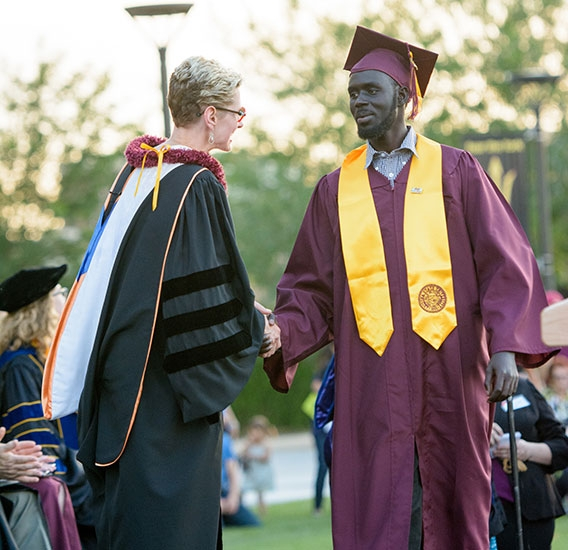 dean shaking hands with student at graduation