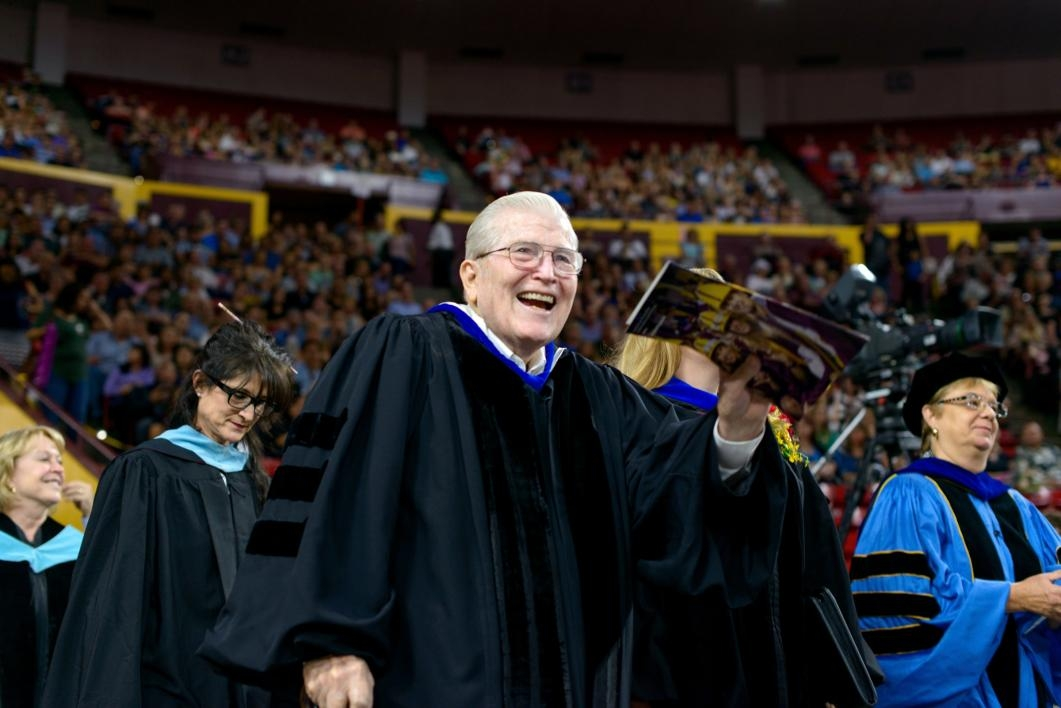 man waving to commencement crowd