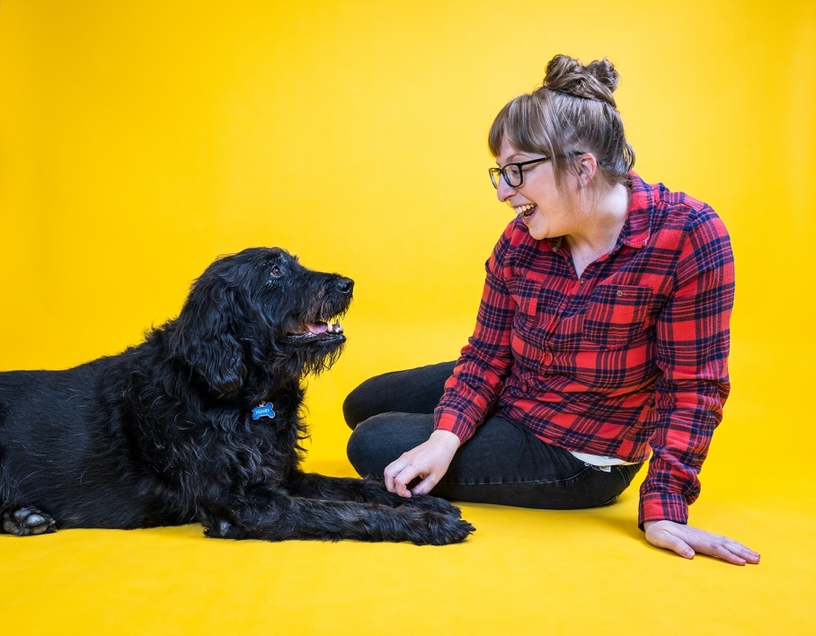 woman smiling at large black dog against yellow background