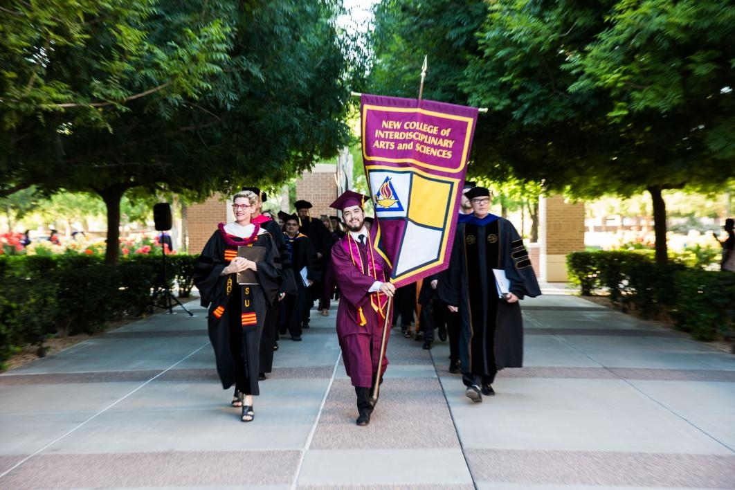 student holding flag walking to convocation