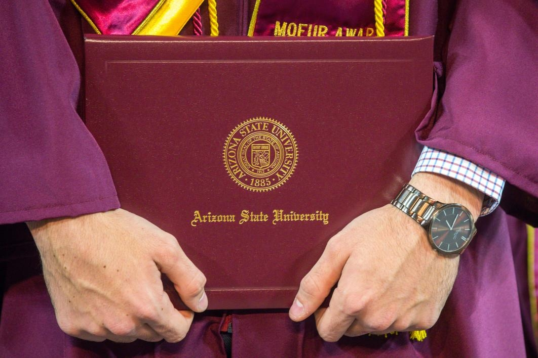 student holding diploma case