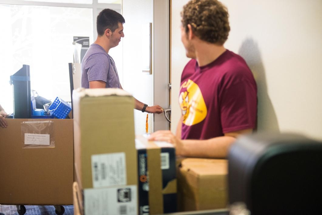 Volunteers help a student move his belongings into the dorm on the Polytechnic campus.