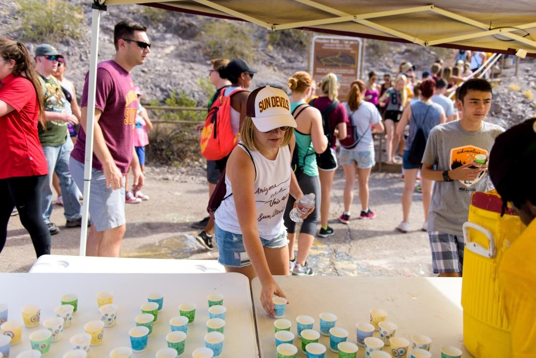 Students grab a dixie cup full of white paint