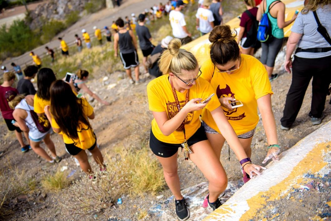 Students flash the ASU pitchforks and snap photos at A mountain