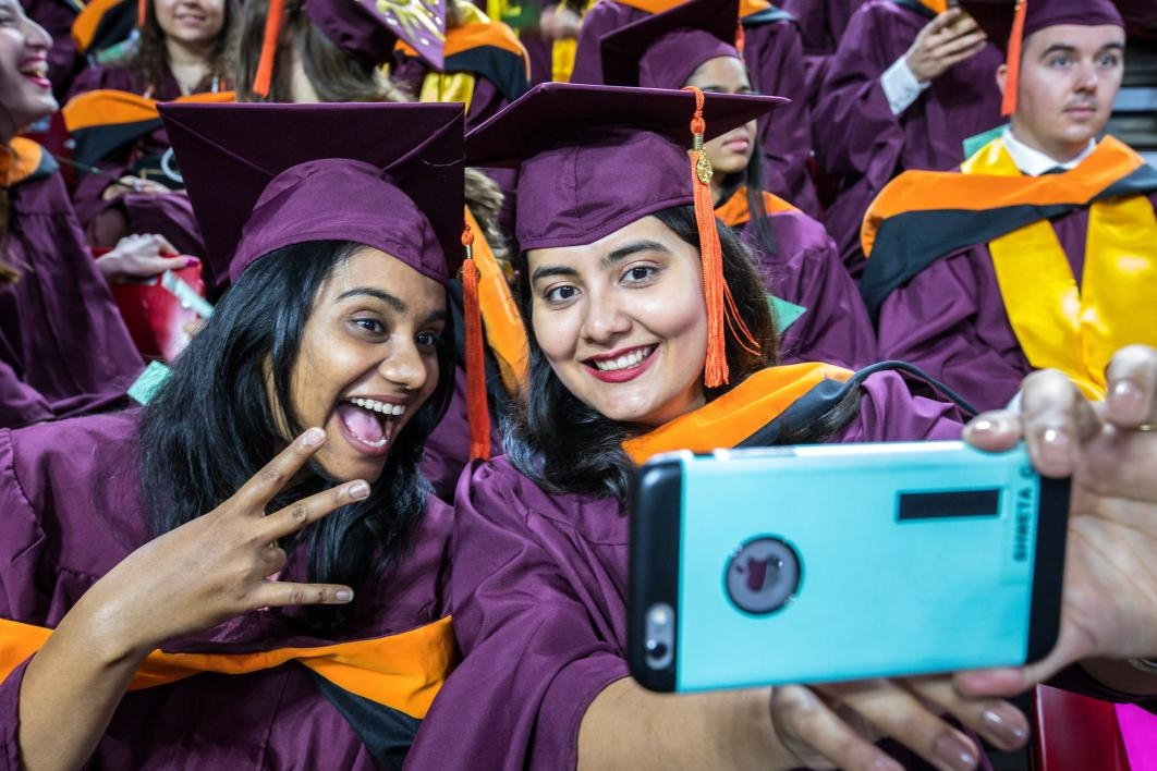 two graduates taking a selfie