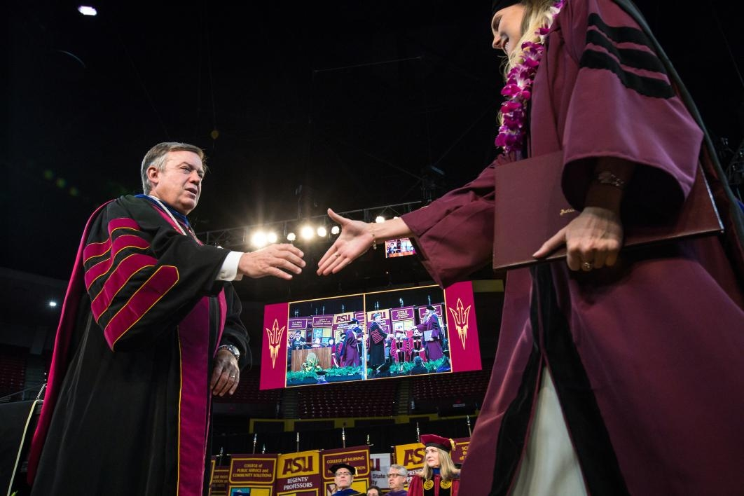 ASU President shaking hands with graduate