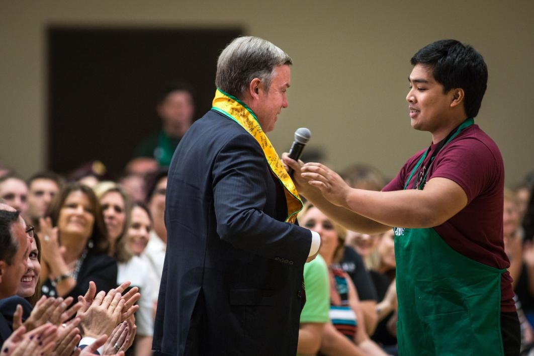 graduate placing stole on ASU President Michael Crow